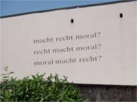 """Zwischen Amtsgericht und evangelischer Stiftskirche steht auf der Wand """"macht recht moral? recht macht moral? moral macht recht?"""""""