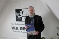 """Dr. Jüregen Fischer mit den Buch """"100 x kleine Geschichte(n) an der VIA REGIA"""" in der Hand."""