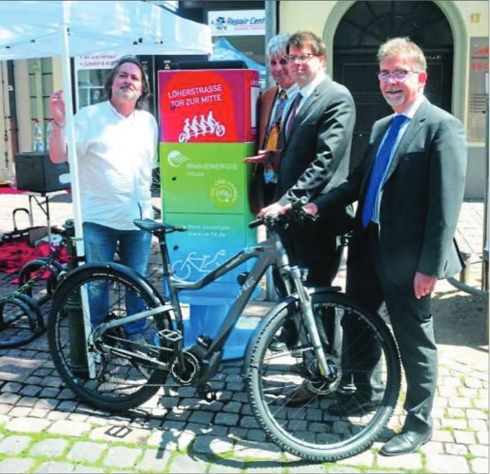 Ab sofort können hier die Rad-Akkus aufgeladen werden [von links]: Thorsten Mager und Clemens Böcher von der IG Löherstraße, OB Heiko Wingenfeld und RhönEnergie-Chef Martin Heun weihen die neue Ladestation ein.