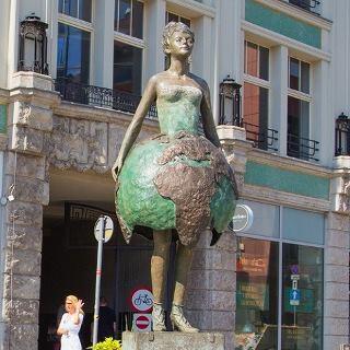 """Für das Vier Tempel Viertel schuf die Bildhauerin Ewa Rossano die Skultur """"Kristallplanet"""", die 2012 enthüllt wurde. Die zwei Meter große Figur eines Mädchens im Kleid, das an eine Erdkugel erinnert, symbolisiert die Einheit der Welt, trotz religiöser und kultureller Unterschiede."""