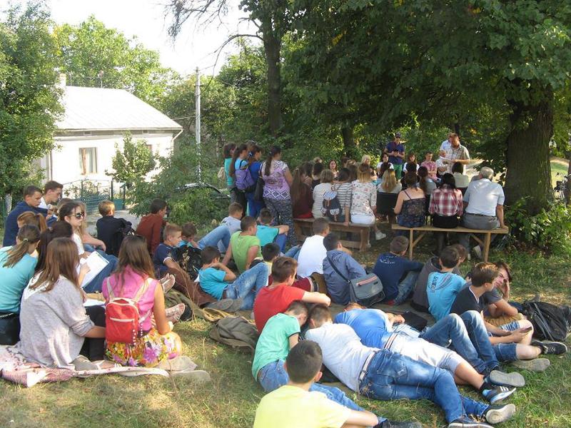 Leute sitzen auf einer Grünenfläsche und Hören zu.